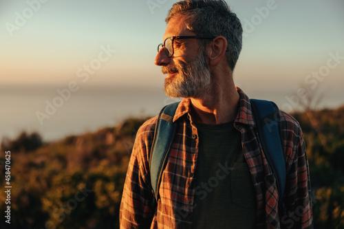 Fototapeta Adventurous male hiker looking away while standing on a hilltop