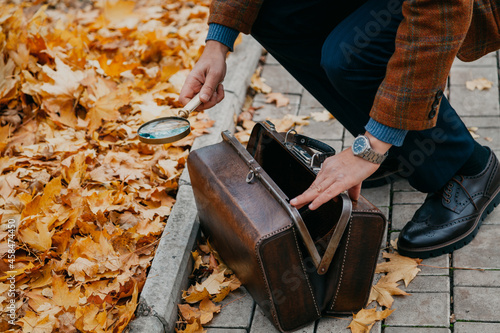Carta da parati Hands take out magnifying glass from leather carpetbag on autumn alley