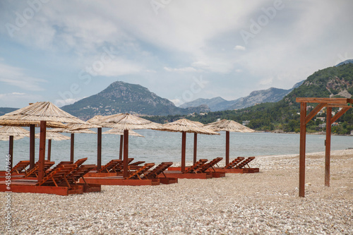 Fototapeta Beach with umbrellas and sun loungers by the sea on a sunny day, Montenegro