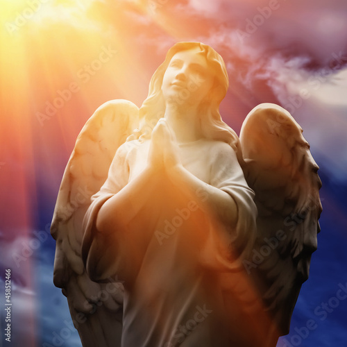 Beautiful angel with wings looking up at the sky in rays of light Fotobehang