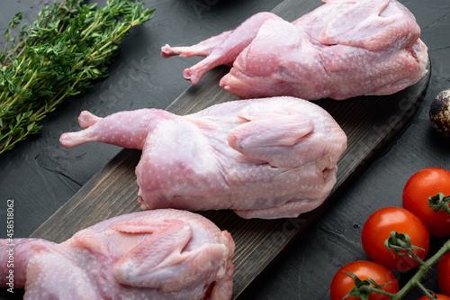 Fototapeta Whole quails with spices, herbs, vegetables, on black textured background