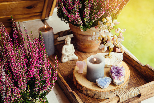 Fotografiet Spiritual home balcony decor with heather flowers, candlelight flame, crystal geodes, crystal wire tree and small Buddha figurine