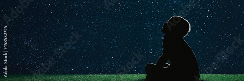 child sit on the grass at night and look at the christmas night sky Fototapete