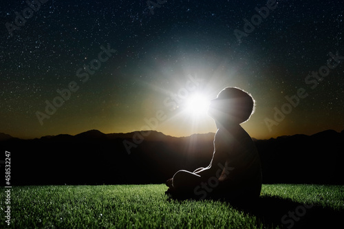 Obraz na plátně a child sits on a mountain top at sunset and dreams