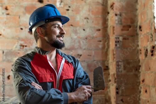 Fotografija Bricklayer poses smiling while renovating a bathroom