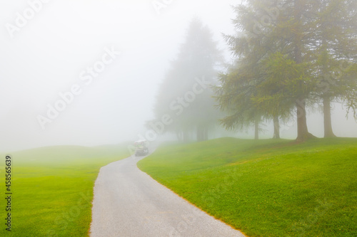 Canvas Print Crans Sur Sierre Golf Course with a Golf Cart and Fog in Crans Montana