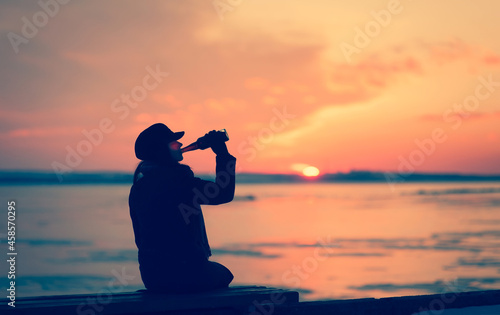 Fotografiet A silhouette of young caucasian girl sits on a bench and drinks alcohol alone