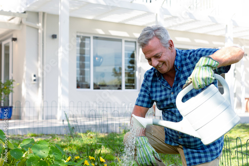 Happy caucasian senior man wearing gloves and watering plants