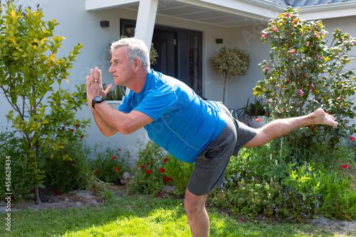 Focused caucasian senior man practicing yoga in garden