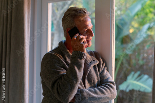 Happy caucasian senior man standing at window and making call