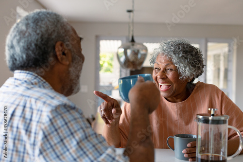 Happy african american senior couple sitting in kitchen with coffee and talking