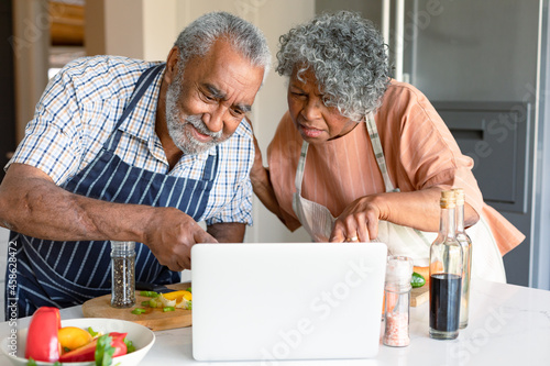 Happy arfican american senior couple preparing meal together and using laptop