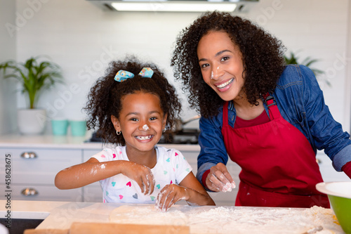 Happy african american mother and daughter baking together in kitchen