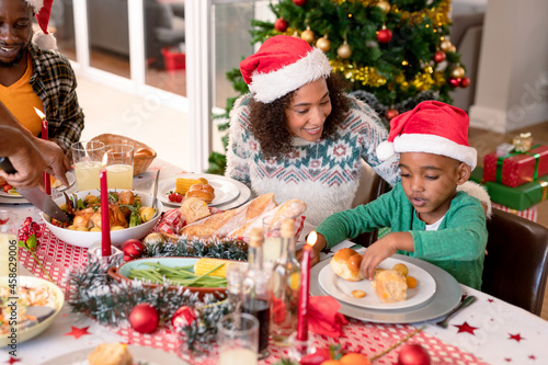 Happy african american mother and son wearing santa hats at christmas table