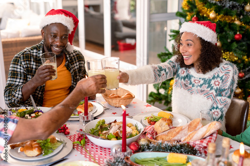 Happy african american couple wearing santa hats, making toast at christmas table