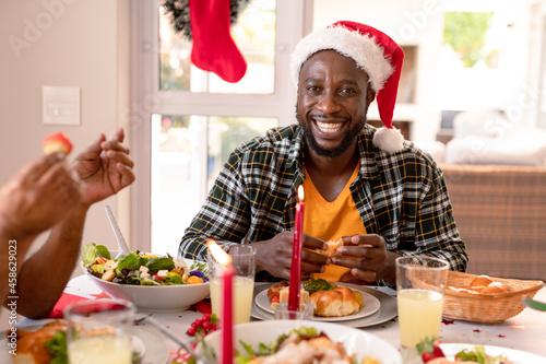 Happy african american man wearing santa hat sitting at christmas table