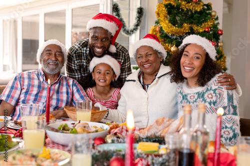 Happy multi generation family wearing santa hats, taking photo