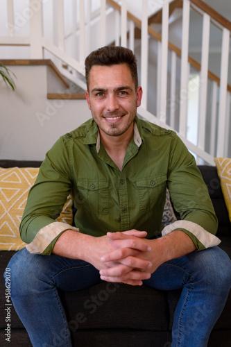 Happy caucasian man sitting on sofa and looking at camera