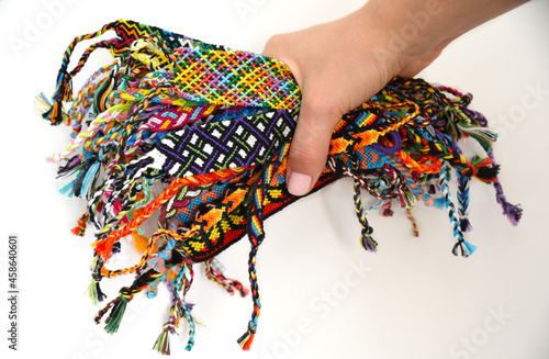 Canvas-taulu Female hand holding many woven multi-colored DIY friendship bracelets handmade of embroidery thread with knots on white background
