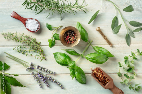 Fototapeta Fresh herbs, shot from above on a wooden background with salt and pepper