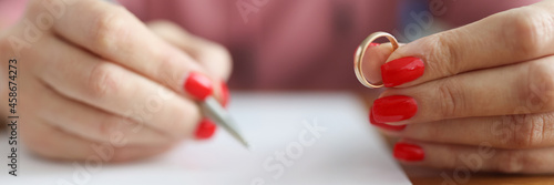 Woman is applying for divorce and is holding wedding ring Fototapet