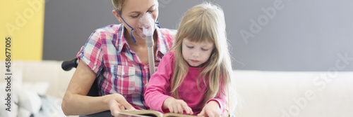 Foto Woman in wheelchair and oxygen mask is reading book with little girl