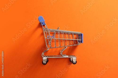 Fotografie, Obraz shopping cart, empty grocery cart on orange background