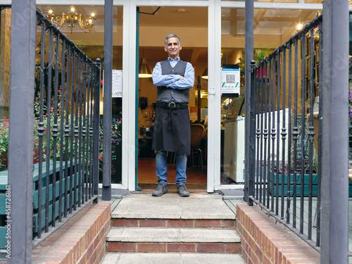 Canvas Print Portrait of cafe owner in doorway