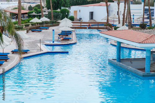 Fotografie, Obraz Swimming pool with sun loungers on site next to the sea.