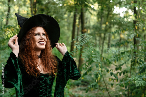 Fototapeta Young witch in green forest