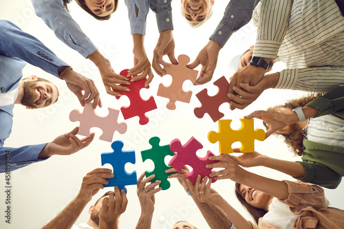 Photo Group of young and mature people making circle of colorful jigsaw puzzle parts, low angle shot from below