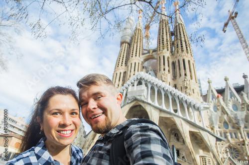 Fotografie, Obraz Happy tourists photographing in front of the famous Sagrada Familia roman cathol