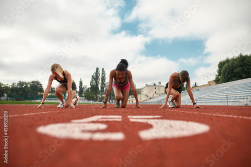 Obraz na plátně Group of three professional female runners starting the race on track field at t