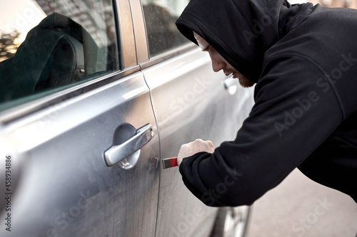 Fotografie, Obraz Unrecognizable Car thief steal car breaking door criminal job burglar Hijacks Auto thief is trying break into automobile using tools