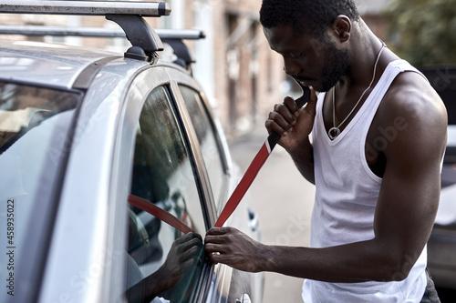 Canvas Print thief steal car breaking door criminal job burglar Hijacks Auto thief in black wear, trying break into automobile using tools