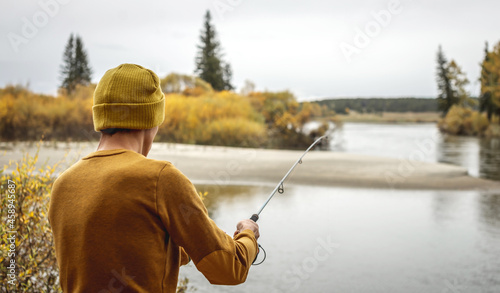 Canvas Print Man in a yellow sweater and hat is fishing on the river bank in the autumn fores