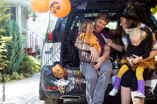 Photo Diverse family friends celebrating Halloween in car trunk outdoors