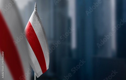 Fototapeta Small flags of Belarus on a blurry background of the city