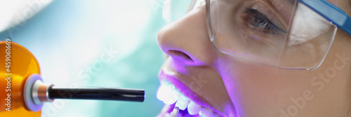 Fotografia Doctor dentist shining on teeth of female patient curing light closeup