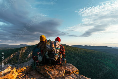 Obraz na plátně Two travelers are sitting on the edge of a cliff and admiring the beautiful panoramic view