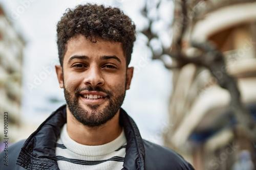 Young arab man smiling outdoor at the town Fototapeta
