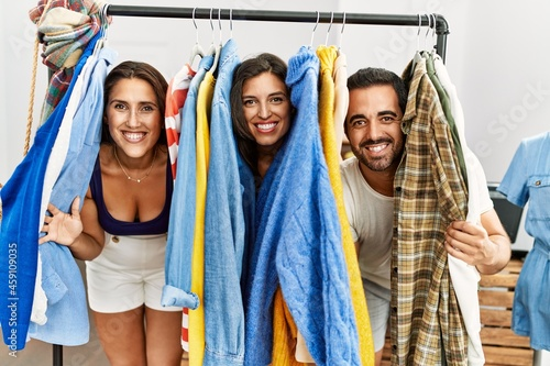 Photo Young hispanic people smiling happy appearing through clothes at fashion store