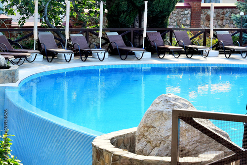 Fotografie, Obraz View of the pool, sun loungers and parasols among lush green palms and bushes in