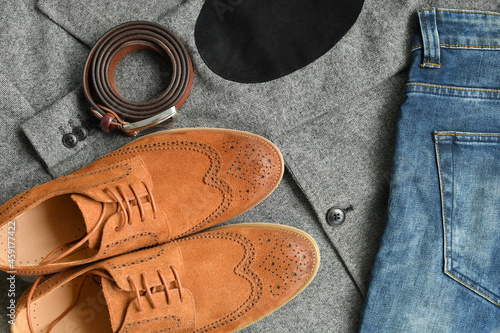 A pair of brown suede derby shoes and jeans on tweed blazer background Fotobehang