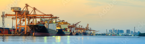 Fotografie, Obraz Panorama image of container cargo ship with ports crane bridge in harbor and ref