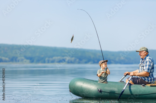 Fototapeta grandfather with grandson together fishing from inflatable boat