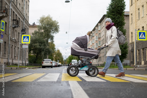 Fotografie, Tablou Woman with stroller on crosswalk crossing the road looking aside checking cars