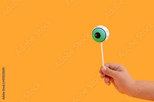 Canvas Halloween concept with human doll eyeball as lollipop