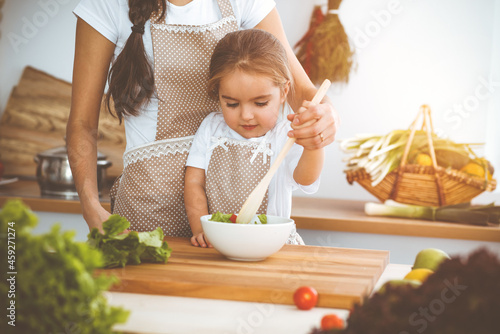 Fototapeta Happy woman and her daughter making healthy vegan salad and snacks for family feasting in sunny kitchen
