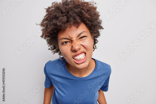 Fotografiet Close up shot of displeased African American woman frowns face clenches teeth from anger dressed in casual blue t shirt expresses negative emotions poses against white background